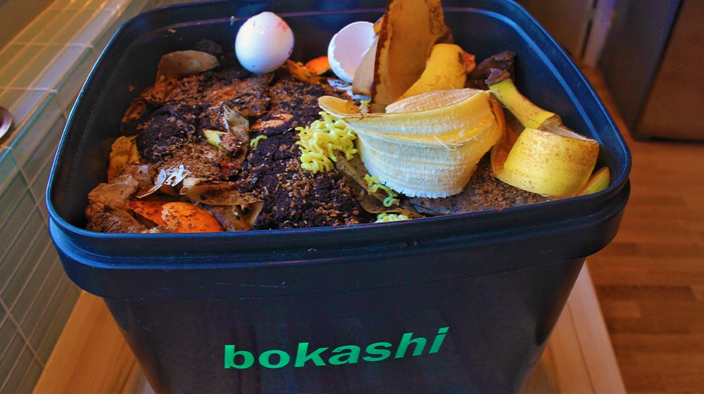 A bucket filled with bokashi | Everything You Need To Know About Bokashi Composting | food scraps | featured
